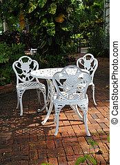 white garden chairs in a backyard patio