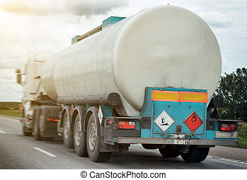 White gas tanker truck on highway in motion.