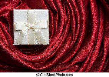 White gift box on red silk