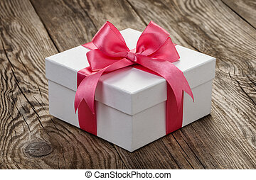 White gift box with a pink ribbon on the old board