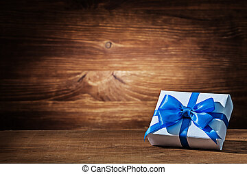 white gift box with blue ribbon on vintage wood