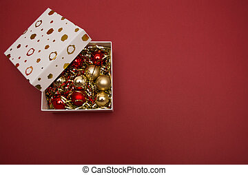 white gift box with Christmas toys and tinsel on red background