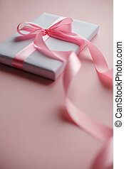 White gift box with pink bow on a pink background