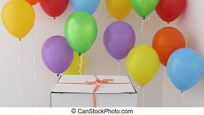 White gift box with red ribbon and colorful balloon on white...
