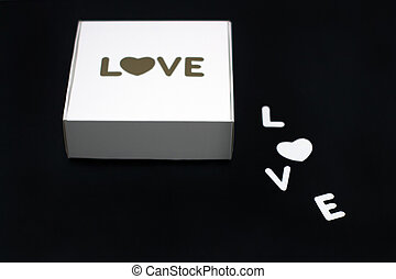 white gift box with the word love on a black background