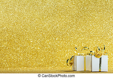 White gift boxes with ribbon on sparkling gold glitter background