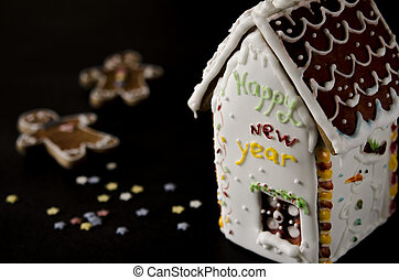 White gingerbread house with a brown roof, a window and the inscription happy New Year on a white wall
