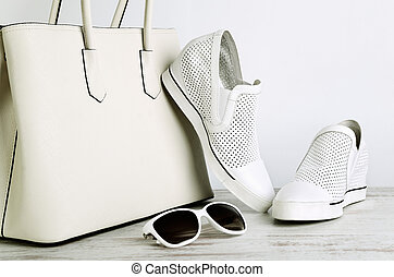 White girls handbag, shoes and sun glasses on a light background horizontal