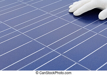 White gloved hand in front of solar cells