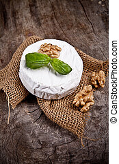 White goat cheese with noble rot on wooden table