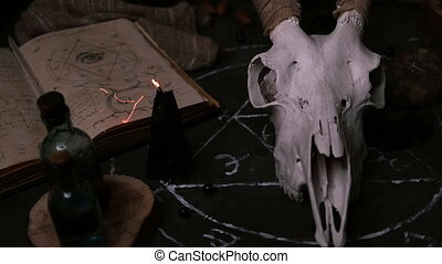 White goat scull with horns, old book, black candles. Halloween decoration.