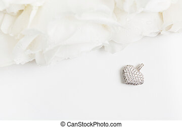 White golden pendant with diamonds and bouquet of white roses with copy space. Flat lay. Top view. Mockup