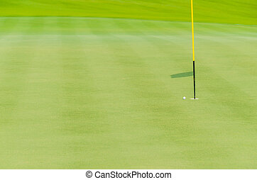 white golf ball on green near hole