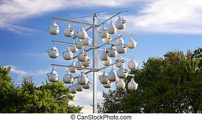 White Gourd Bird Houses Hanging From Pole