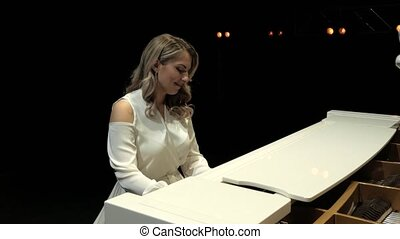White grand piano on a stage. Nice smiling woman pianist ...