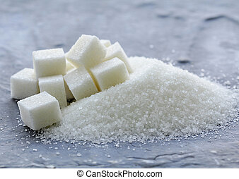 white granulated sugar and refined sugar on a gray ...
