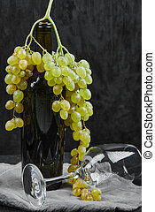 White grapes around a bottle of wine and an empty glass on dark background