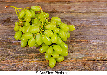 White grapes in an old wooden background.