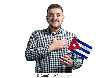 White guy holding a flag of Cuba and holds his hand on his heart isolated on a white background With love to Cuba