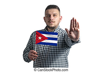 White guy holding a flag of Cuba and with a serious face shows a hand stop sign isolated on a white background