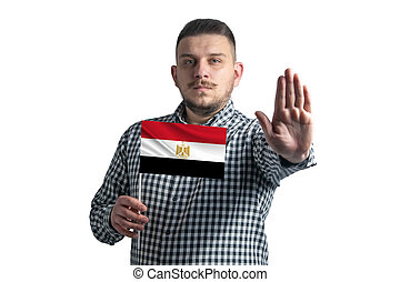 White guy holding a flag of Egypt and with a serious face shows a hand stop sign isolated on a white background