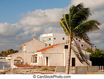 White Hacienda on a Beach - A white stucco house with a red...