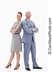 White hair businessman back to back with a woman and smiling