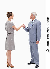 White hair businessman smiling face to face and shaking hands with a woman against white background