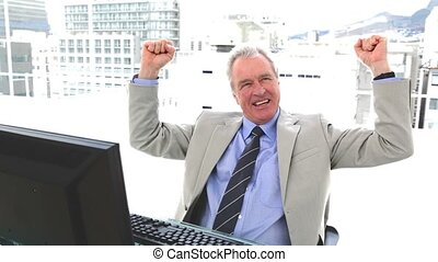 White hair businessman the fists raised sitting in his...