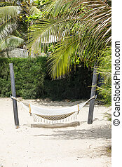 White hammock hangs on a sandy beach