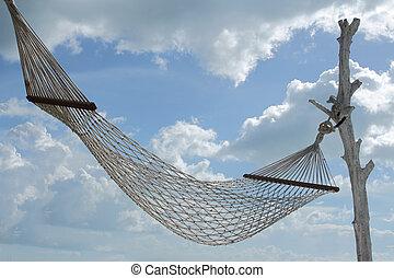 white hammock over blue sky white cloud background