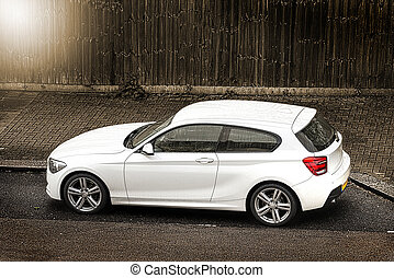 White hatchback car parked in the street