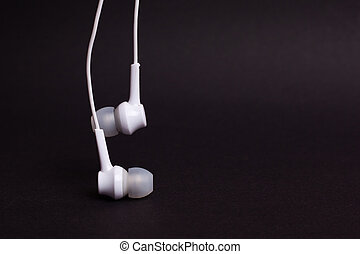 White headphones on a dark background with copy space