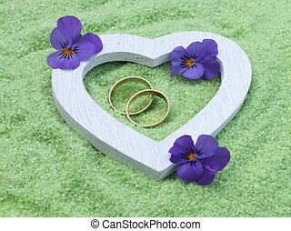 white heart and wedding rings made of wood with delicate blossoms in small stones