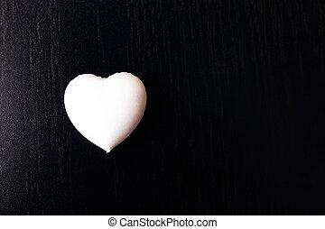 White heart on a black background closeup