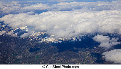 White heavy clouds background hanging on blue sky over mountain. Aerial photo from plane's window.