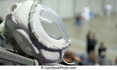 White helmet of fighter KUDO against sportsmen training in hall