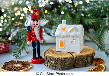 White house in the form of a ceramic candlestick on the background of decorative branches with a Nutcracker figure-Christmas card.