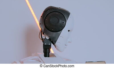 White humanoid robot moving head at technology exhibition....