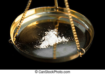 White illegal substance being weighed on black background