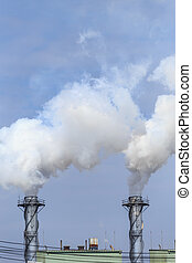 White industrial steam in factory on blue sky