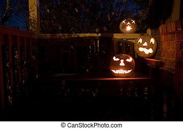 White jack o\'lanterns on a bench at night - Three lit white...