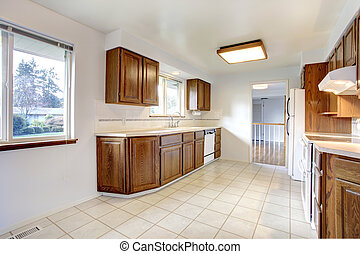 White kitchen room with windows, tile floor,  brown storage combination and white appliances