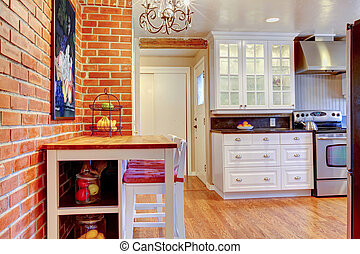 White kitchen with brick wall, hardwood and stainless steal...