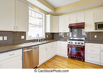 White kitchen with burgundy stove and grey counter tops -...