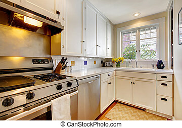 White kitchen with stainless steal appliances.
