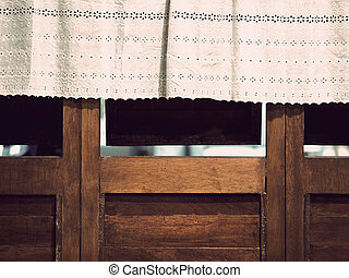White lace curtain with small flower pattern at the window