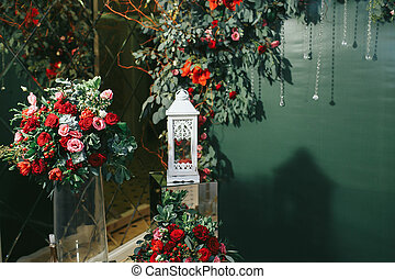 White lantern stands in the front of green background and red flowers
