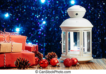 White lantern with a burning candle and boxes with gifts on the background of the Christmas tree with lights. Beautiful christmas or new year background