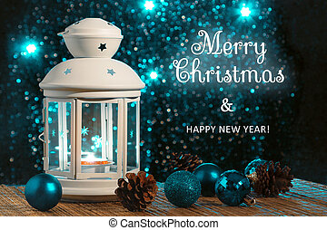 White lantern with a burning candle and ornament on the background of the Christmas tree with lights. Beautiful background with an inscription Merry Christmas and Happy New Year